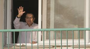 Hosni Mubarak waves to supporters from his room at the Maadi Military Hospital (AP)