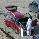 Police investigators inspect a car near the river in Antwerp (AP)