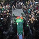 Masked gunmen from the Qassam brigade, the militia wing of Hamas, carry the body of Mazen Faqha during his funeral in Gaza City (AP)