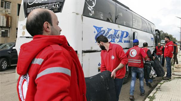 Members of the Syrian Red Crescent assist in the departure of opposition fighters and their families as they prepare to leave the al-Waer area (AP)