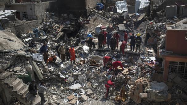 Civil protection rescue team work on the debris of a destroyed house in Mosul (AP)