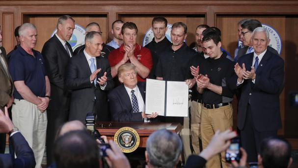 President Donald Trump is applauded as he holds up the signed Energy Independence Executive Order (Pablo Martinez Monsivais/AP)