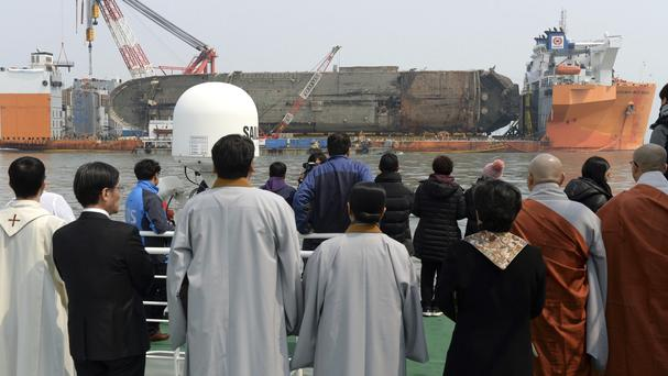 Relatives of missing victims attend religious services on a boat near the sunken ferry Sewol (Yonhap/AP)