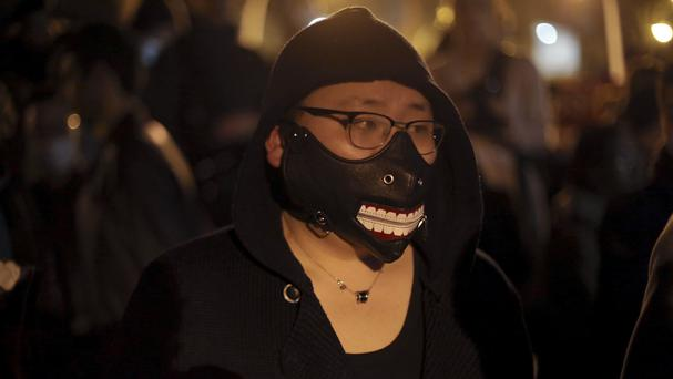 A Chinese immigrant wears a mask during a protest over the fatal shooting of a Chinese man in his apartment, in Paris. (AP/Thibault Camus)