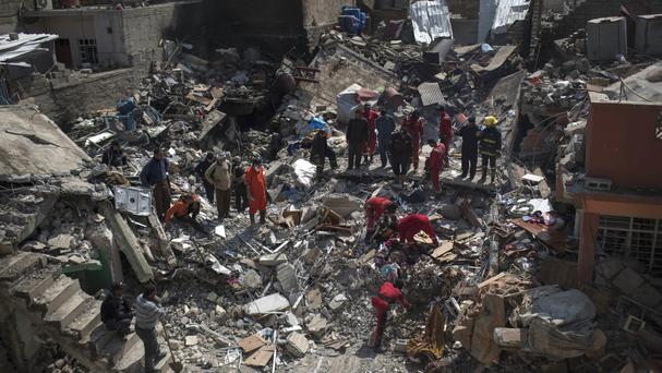 Civil protection rescue teams work on the debris of a destroyed house on the western side of Mosul, Iraq (AP)