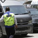An unidentified van believed to be carrying the body of Kim Jong Nam comes out from the forensic department at Kuala Lumpur Hospital (Daniel Chan/AP)