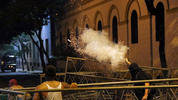 A protester aims a firework at police outside the congress building (AP)