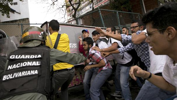 Venezuelan officers are confronted by university students during a protest outside the Supreme Court in Caracas (AP)