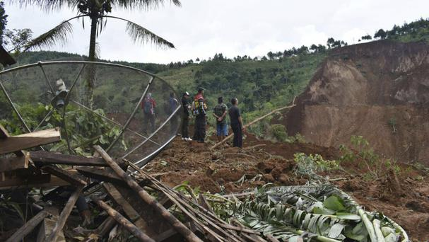 Rescuers search for victims in an area hit by a landslide in the village of Banaran, Ponorogo, East Java (AP)