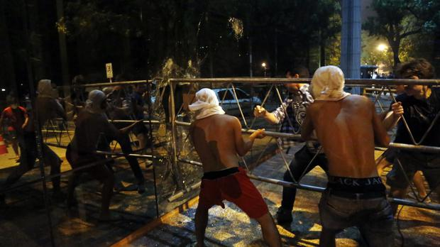 People ram a barrier into the Congress building during clashes in Asuncion (AP)