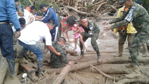 Soldiers rescue a girl in Mocoa after an overflowing river swept through the city (Colombian National Army/AP)