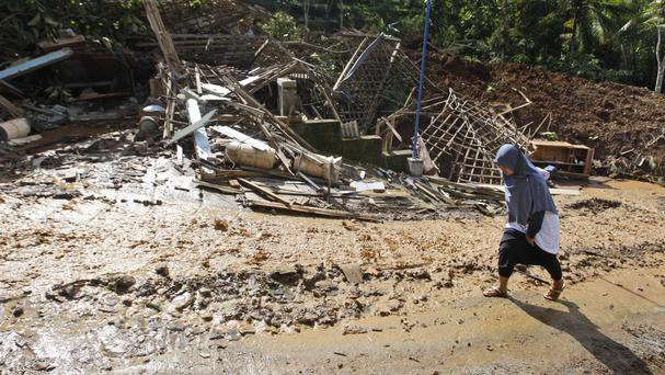A woman walks past houses destroyed by a landslide in the village of Banaran, Ponorogo, East Java, Indonesia (Trisnadi/AP)