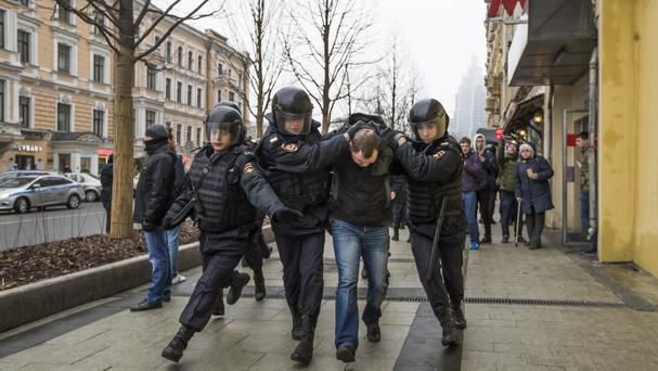 Police officers detain a man in Moscow (AP)