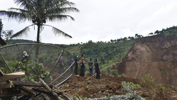 Rescuers search for victims after a landslide in the village of Banaran, Ponorogo, East Java, Indonesia (Firdaus/AP)
