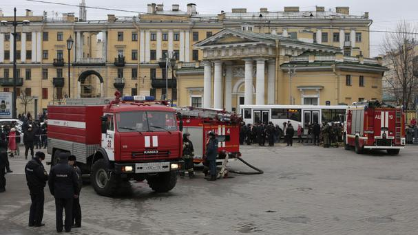 Police and emergency service officers stand near fire engines at Sadovaya Square in St Petersburg (Evgenii Kurskov/AP)