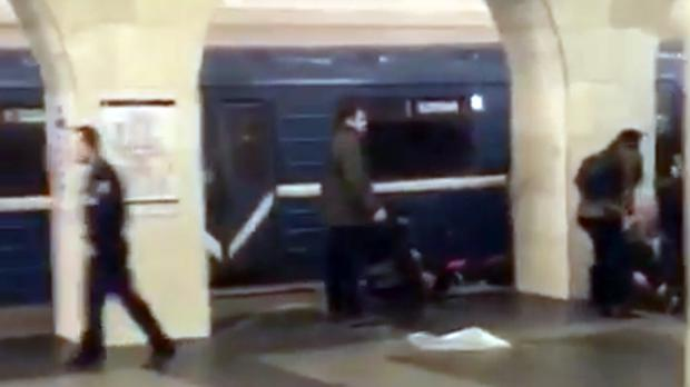 A police officer, left, and people walk past the damaged train at the Tekhnologichesky Institut subway station in St Petersburg (AP video via AP)