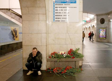 A man at Tekhnologichesky Institut metro station in St Petersburg sits by a memorial for victims of the blast. Photo: Grigory Dukor/Reuters