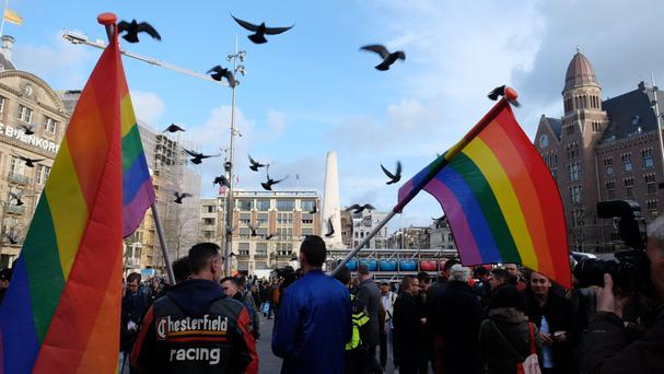 Protesters march through the Dutch capital Amsterdam to show solidarity with two gay men who were beaten over the weekend (AP)