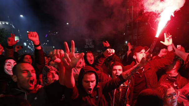 Demonstrators light torches during a protest march in Belgrade, Serbia (AP)