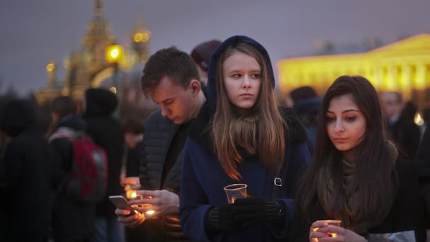Young people hold candles in memory of the victims of the St Petersburg subway bombing (AP Photo/Yevgeny Kurskov)