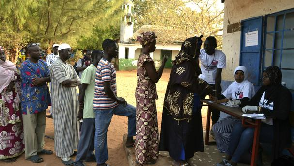 Gambians wait to cast their vote at a polling station (AP)