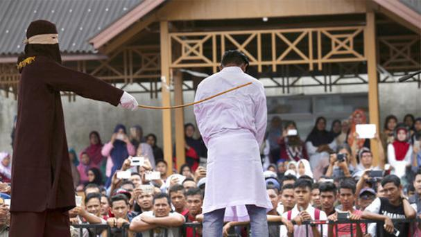 A Sharia law official whips a man with a rattan cane in Banda Aceh, Indonesia. (AP/Heri Juanda)