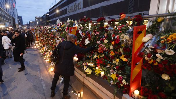 A woman places a flower on a fence following Friday's terror attack in central Stockholm, Sweden (AP/Markus Schreiber)