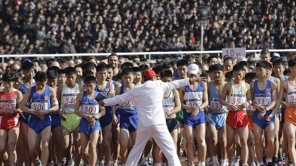 A race official stops eager participants from crossing the starting line prematurely during the Pyongyang marathon (AP)