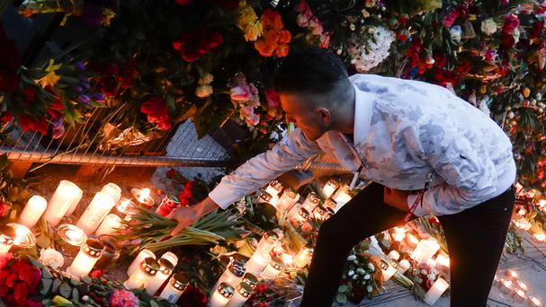 A man places flowers at a site near the department store (AP)