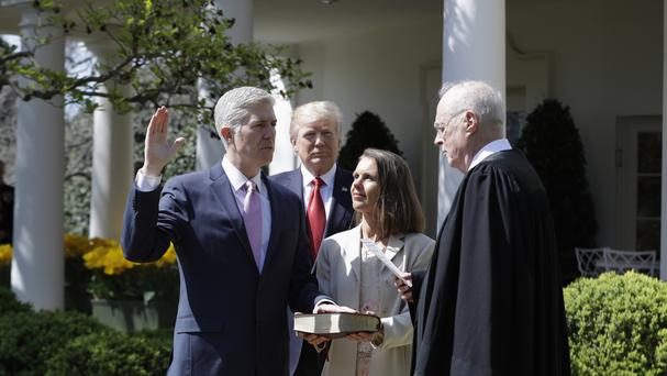 President Donald Trump watches as Supreme Court Justice Anthony Kennedy administers the judicial oath to Neil Gorsuch in the Rose Garden of the White House