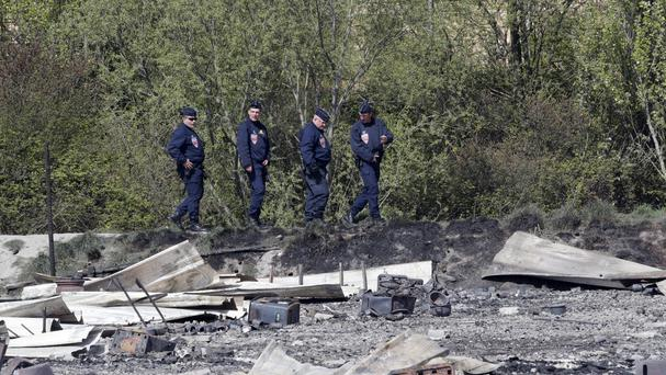 Police officers patrol the burned remnants of a migrant camp in northern France (AP/Christophe Ena)