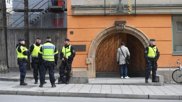 Police with automatic weapons guard the entrance to Stockholm District Court in Sweden (Fredrik Sandberg/TT via AP)