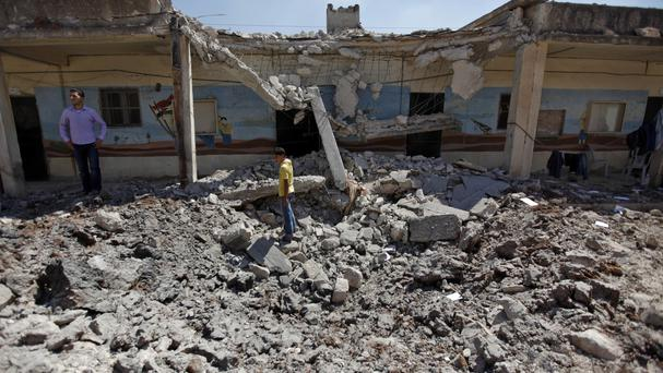 Syrians check the damage to a school after it was hit by an air strike in Tal Rifat on the outskirts of Aleppo (AP/ Khalil Hamra)