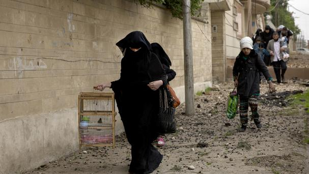 An Iraqi woman carries a bird as she flees heavy fighting in Mosul (AP/Maya Alleruzzo)