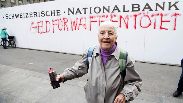Louise Schneider poses for the media after spraying the wall of the Swiss National Bank in Bern (Anthony Anex/Keystone via AP)