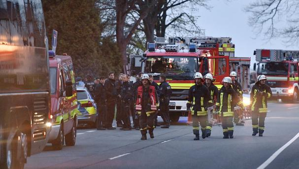 Police officers and firefighters stand outside the Dortmund team bus after it was damaged in an explosion (AP)