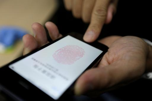 A journalist tests the iPhone 5S Touch ID fingerprint recognition feature at Apple