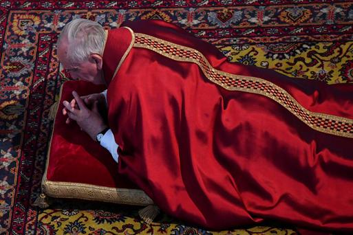 Pope Francis lies as he prays during the Celebration of the Lord's Passion in St Peter's Basilica in Rome yesterday. Photo: Reuters