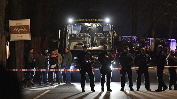Police officers stand in front of Dortmund's damaged team bus after explosions which injured two people (AP)