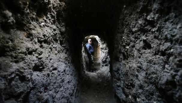 A Syrian army soldier makes his way in a tunnel reportedly previously used by rebel fighters (Hassan Ammar/AP)