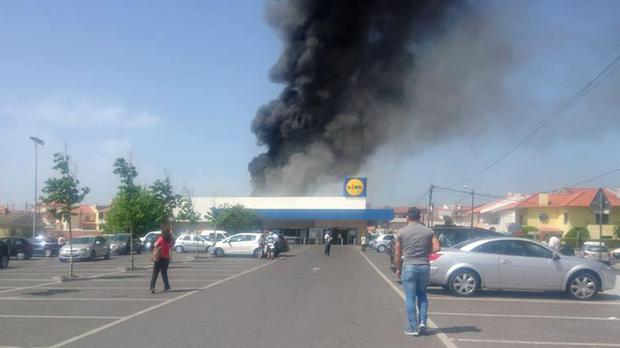 Photo taken with permission from the Facebook page of Fabio Miguel of smoke rising behind a Lidl supermarket near Lisbon after a small plane crashed