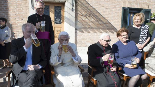 Pope Emeritus Benedict XVI and his brother Georg, centre, enjoy a large glass of here (L'Osservatore Romano/Pool Photo via AP)
