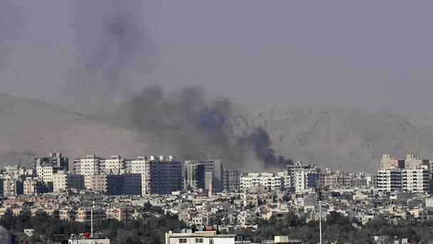 Smoke from heavy shelling in Barzeh, a suburb of Damascus, Syria, in August 2013 (AP Photo/Hassan Ammar, File)