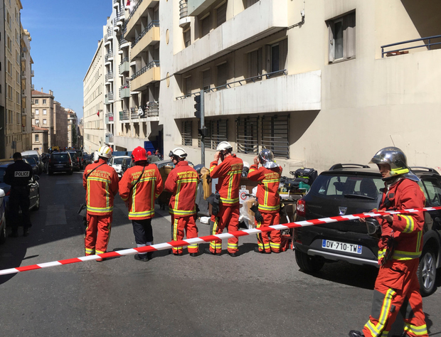A police officer and rescue workers cordon off a street during searches Photo: AP Photo/Claude Paris