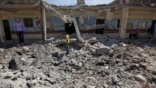 Syrians check the damage to a school after it was hit by an air strike in Tal Rifat (AP/ Khalil Hamra)