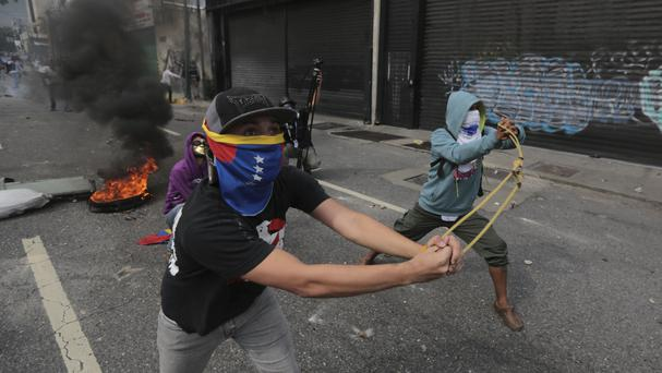 Anti-government protesters launch stones with a sling during clashes in Caracas, Venezuela (Fernando Llano/AP)