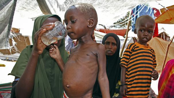 A Somali mother gives water to her malnourished son at a camp in the Sahal area on the outskirts of Mogadishu (Farah Abdi Warsameh/AP)
