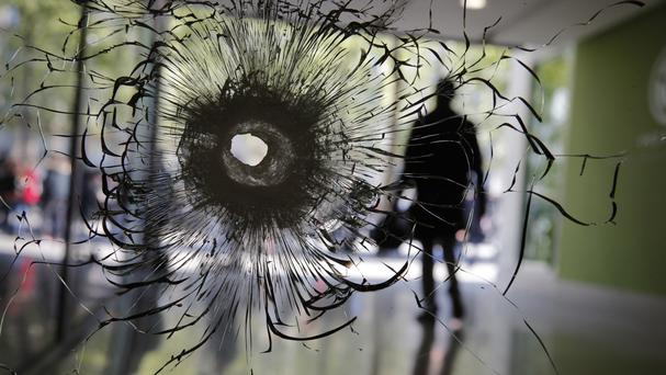 A bullet hole left in the window of a shop on the Champs Elysees in Paris (Christophe Ena/AP)