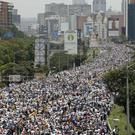 Anti-government protesters march along a highway in Caracas (Ariana Cubillos/AP)