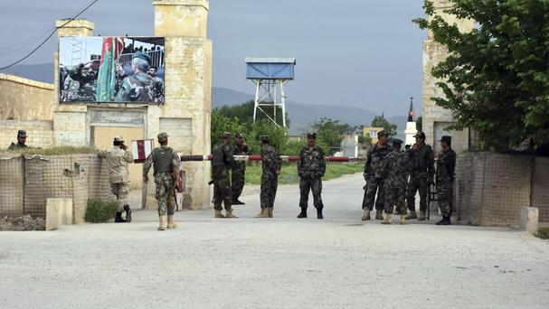 Afghan soldiers at the gate of a military compound after an attack by gunmen (AP/Mirwais Najand)